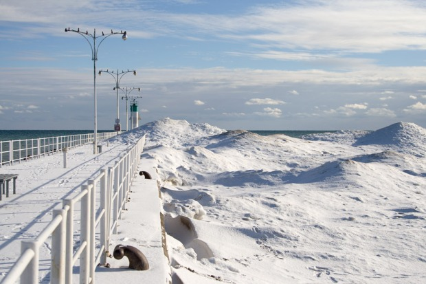 Oshawa's lighthouse pier with hills of snow and ice.